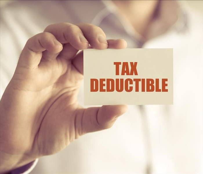 Closeup on businessman holding a card with text TAX DEDUCTIBLE