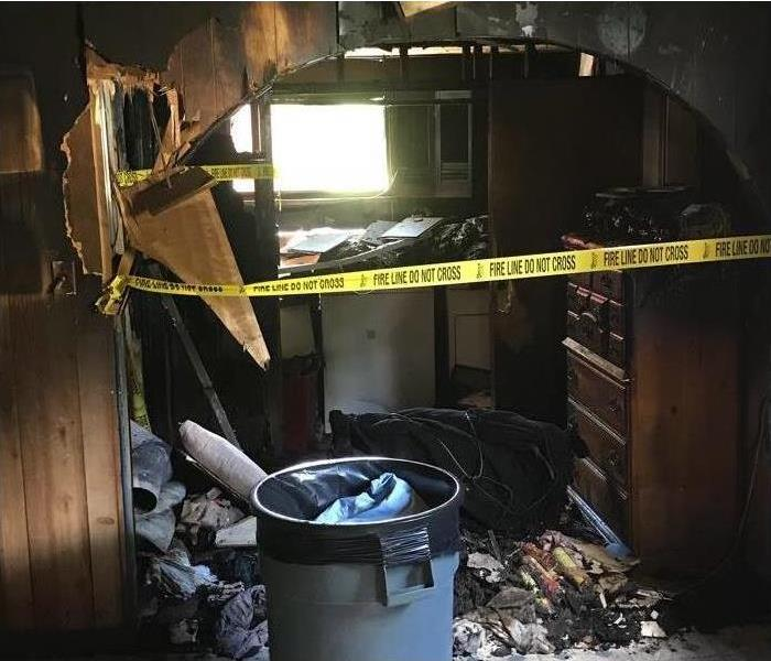 Completely burned bedroom wall, garbage can, yellow no-pass-through strips placed on the home.